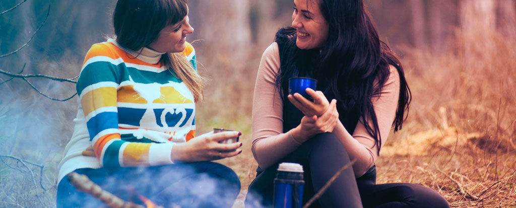 Friends having coffee over campfire