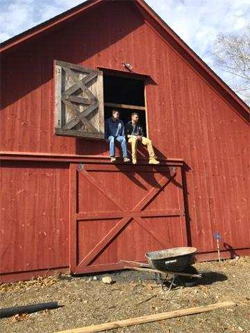 guests sit in the door of the barn at high watch